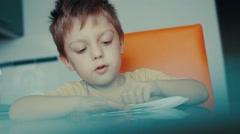 A little boy makes a paper plane Stock Footage
