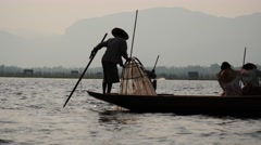Fishers silhouette on boat in waters at Inle lake - view from rocking boat Stock Footage
