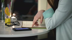 Girl checking something in her journal and answer phone, steadycam shot Stock Footage