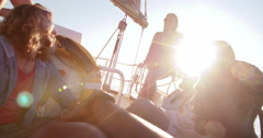 Girl friends drinking beer on sunset yacht cruise with sunflare - stock footage