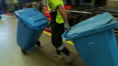 Trash rubbish garbage collection - man wheels blue recycling bins Stock Footage