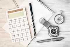 Compass, pocket watch, calculator, notepad, ruler, pen and pencil on the wood - stock photo
