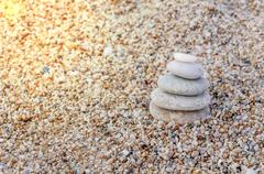 Stack of zen stones on beach background with burning sun Stock Photos
