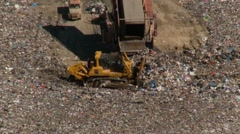 Trash rubbish garbage dump in old mine - pan with bulldozer Stock Footage
