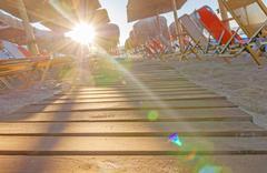 Sunbed, straw umbrella on beautiful beach background with burning sun Stock Photos