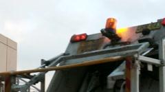 Trash rubbish garbage truck reverses, tilt to flashing light Stock Footage