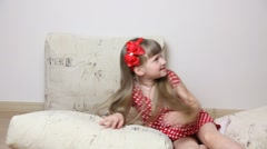 Little girl falling on pillows and man proposing help to her Stock Footage