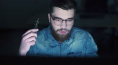 Man smoking electronic cigarette and using PC - stock footage
