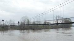 The man walking over suspension bridge, flooded river rushing, tracking shot. Stock Footage