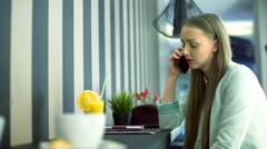Girl talking on cellphone in the cafe and lost signal Stock Footage