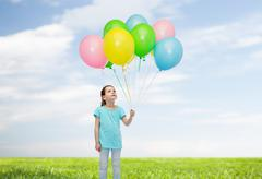Stock Photo of girl looking up with bunch of helium balloons