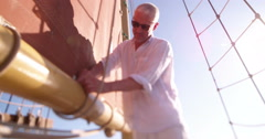 Mature man attending to the main sail on his yacht Stock Footage
