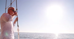 Senior man on a yacht with coffee looking at horizon - stock footage