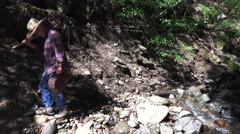 Miner, prospector walking stream bed with gold pan Stock Footage