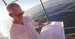 Mature traveler on sailing vessel looking at map and smiling Stock Footage
