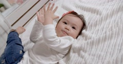 Family idyll,little Asian baby girl laughing on the bed Stock Footage