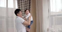 Young Asian father playing with her baby holding, happy emotions, baby laughing Stock Footage