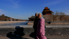 Old men walking past gate tower of Forbidden city Stock Footage