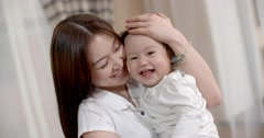 young Asian mother plays with her baby holding, happy emotions, baby laughing - stock footage