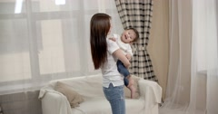 Young Asian mother plays with her baby holding, happy emotions, baby laughing Stock Footage