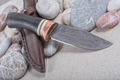 Work knife and a leather pouch on a stone background Stock Photos