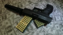 Dolly shot of semi automatic 9mm gun pistol with suppressor on a pile of cash 4k Stock Footage
