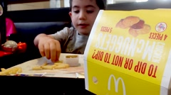 Young boy with eating fries Stock Footage