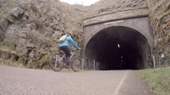 Cyclists enter Headstone tunnel at Monsal Head, Derbyshire, UK Stock Footage