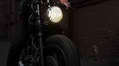 Black custom made cafe racer motorcycle bike. Handsome man sitting on a motor Stock Footage