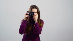 Young girl use old film camera then modern digital in front of white background Stock Footage