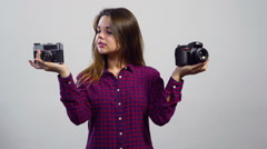 Young girl cant choose between old film and modern digital camera Stock Footage