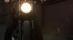 Black custom made cafe racer motorcycle bike. The light from the headlights s Stock Footage