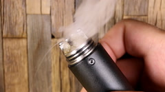 Vaporizer mechanical mod firing with cotton and e-juice - stock footage