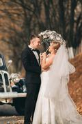 Stylish wedding couple, bride, groom kissing and hugging near retro car in - stock photo