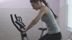 Girl training on a stationary bike Stock Footage