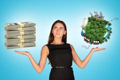 Businesswoman holding cash and earth globe - stock photo