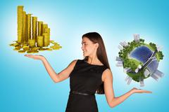 Businesswoman holding coins and earth globe - stock photo