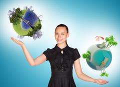 Businesswoman holding two earth globes Stock Photos