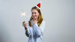 Happy young girl wearing christmas hat and holding a sparkle Stock Footage