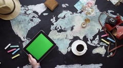Hand, map, compass, money and tablet on the chalkboard table. Stock Footage