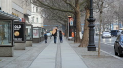 Father, 2 children carry wood on expensive Kurfürstendamm street, Berlin Stock Footage