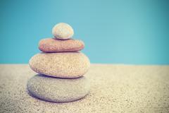 Retro stylized stone pyramid on sand, harmony and balance concept Stock Photos