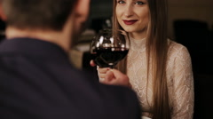 Young happy couple romantic date drink glass of red wine at restaurant - stock footage