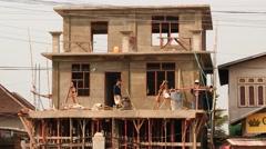 Builders finishing work - Myanmar house building Stock Footage