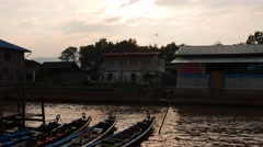 Sunset in Myanmar Inle lake with running boats and buildings silhouette view Stock Footage