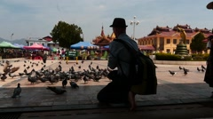 Tourist feeding pigeons near Buddhist temple in Myanmar Stock Footage