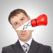Boxing glove beating from businessmans head - stock photo