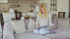 girl look a photo album on the sofa - stock footage
