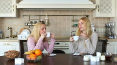 Girls sit on a table in the kitchen talking and drinking tea Stock Footage