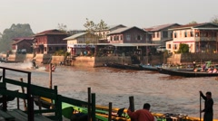 Jetty with people and traditional boats in river - Myanmar Stock Footage